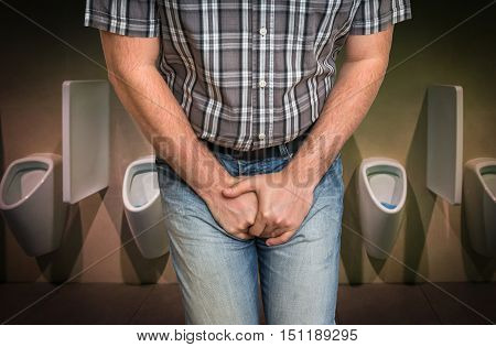 Man with hands holding his crotch he wants to pee in restroom - urinary incontinence concept