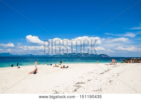 KRABI THAILAND, JANUARY 19, 2015 : Tourists relaxing on the beach on a beautiful day with blue sky, crytal clear water and amazing view of standing huge rock at  Po-da Island in Krabi Thailand