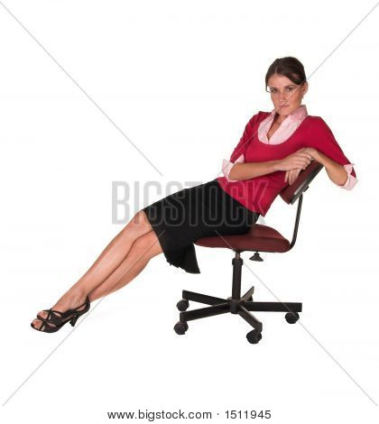Professional Young White Lady Leaning Back In Office Chair, Red Sweater And Black Skirt