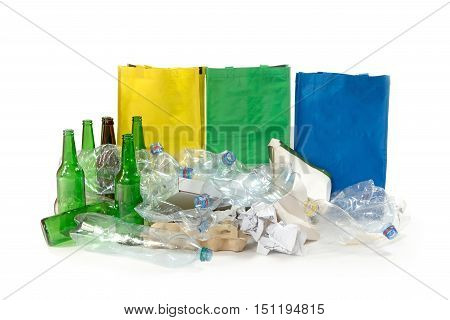Pile of paper waste used plastic and glass bottles are on the white background. Empty yellow green and blue bags are standing behind them.