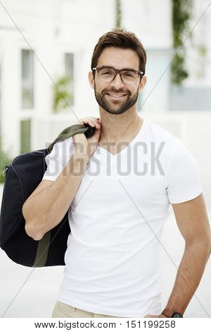 Smiling man with bag and spectacles in town