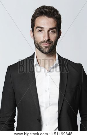 Suave guy in suit smiling -grey background