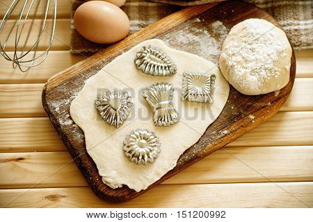 Fresh raw dough and bakeware on a wooden cutting board