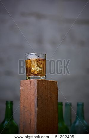 A glass of whiskey with ice on old wooden bar around the old bottles. Shallow dof