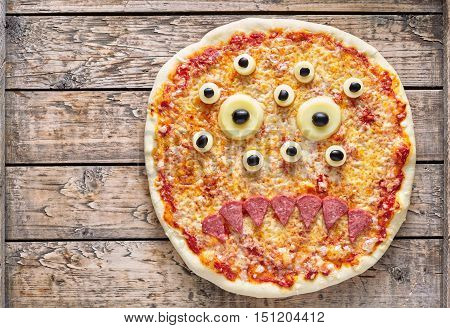 Halloween scary food monster zombie face pizza snack with mozzarella and sausage on vintage wooden table background. Traditional creative holiday celebration party decoration recipe