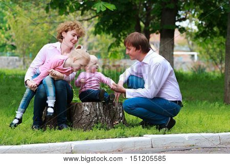 Happy young family spending time together outside in green park