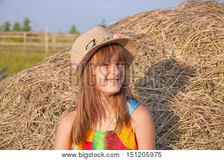 Portrait of naughty, perky, funny little girl with hat on background of haystacks