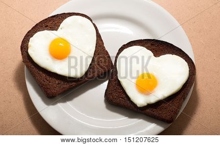 Two Slices of Bread with Fried Eggs in the Shape of Heart on the Plate