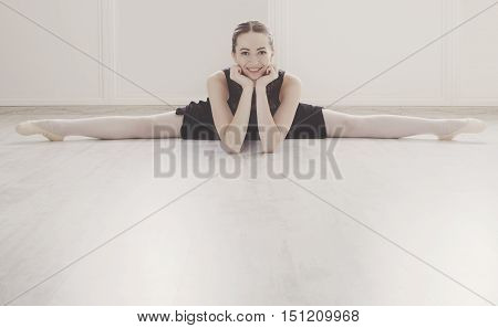 Classical Ballet dancer portrait. Beautiful graceful ballerine in black practice split ballet position in class room background. Ballet class training, high-key soft toning.