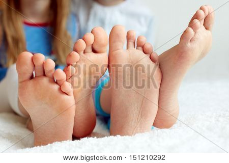 Funny children's foots is barefoot closeup. This is the concept of friendship trust and serenity.
