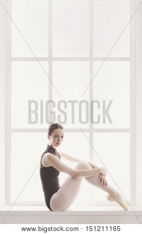 Classical Ballet dancer portrait at window background. Beautiful graceful ballerine in black sits on sill. Ballet class training, high-key soft toning. Vertical image