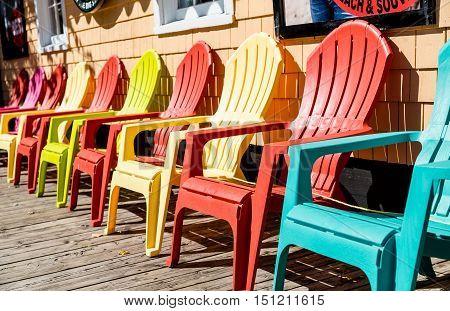 Orange and Yellow Adirondack Chairs on Sidewalk
