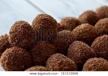 Sweets of dark color. Desserts covered in crumbs. Tasty chocolate rum balls. Biscuit is the main ingredient.