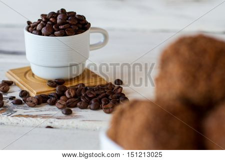 Cup of coffee grains. Dark beans on wooden surface. Main source of caffeine. Get boost of energy.