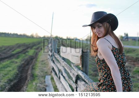 cowgirl in a hat with guitar outdoor