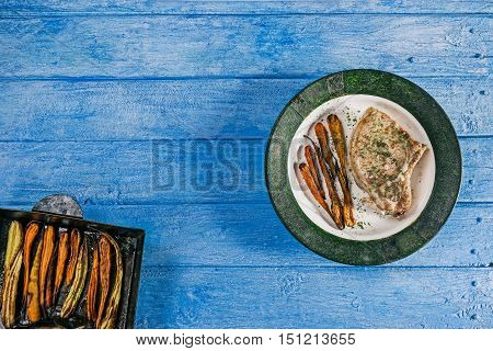 Porkchop and baby carrots baked on metal baking tray and served on the plate