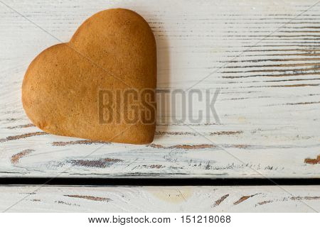 Brown heart shaped cookie. Biscuit on white wooden surface. Send greetings to beloved person. Find the recipe of love.