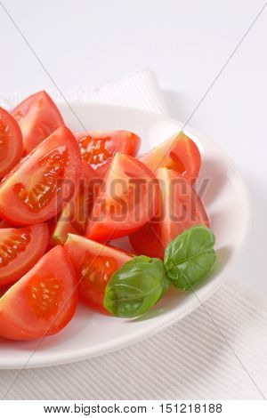 plate of sliced ripe tomatoes on white place mat