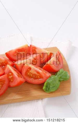 sliced ripe tomatoes on wooden cutting board