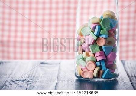 Colorful sweet candy in wine carafe on old wooden table against vintage kitchen dishcloth.