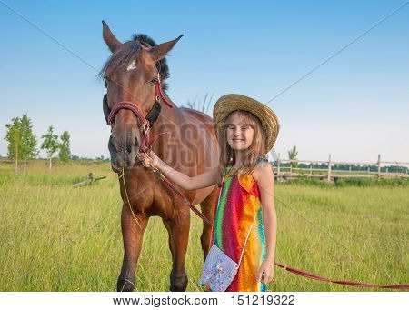 Little girl wearing hat in bright sundress with horse in meadow