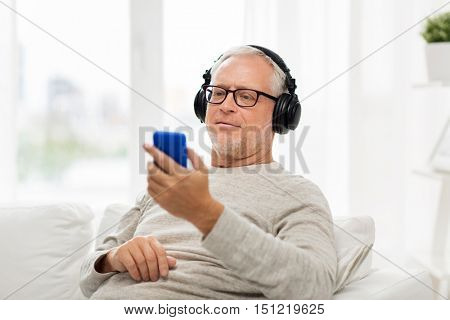 technology, people, lifestyle and distance learning concept - happy senior man with smartphone and headphones listening to music and singing at home