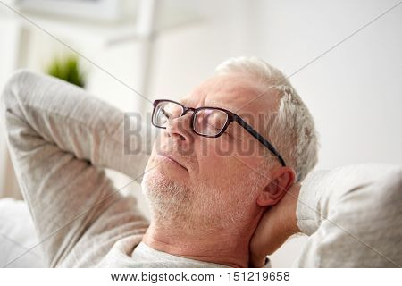 old age, comfort and people concept - senior man in glasses relaxing on sofa at home