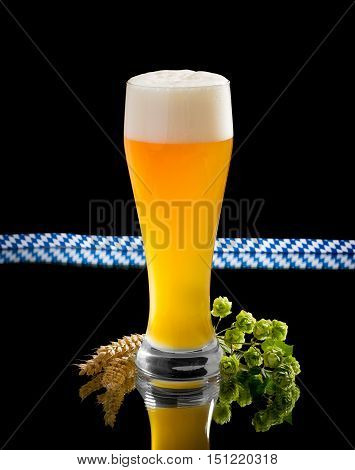 Natural turbid yeast wheat beer in glass with hop and wheat spike on black
