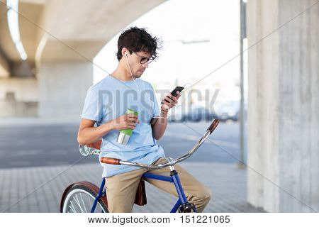 people, communication, technology and lifestyle - hipster man with smartphone, earphones and thermos cup on fixed gear bike listening to music on city street