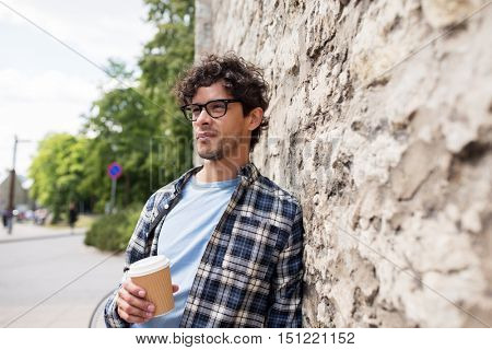 lifestyle, drinks and people concept - man in eyeglasses drinking coffee from disposable paper cup over stone street wall