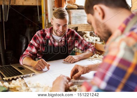 profession, carpentry, woodwork and people concept - two carpenters with laptop computer and blueprint at workshop