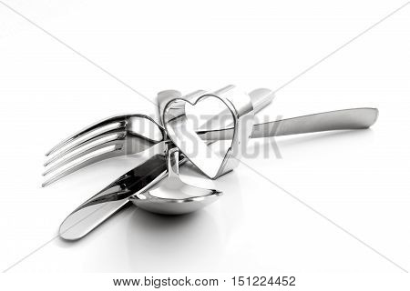 Cutlery, fork, spoon, with knife and heart isolated on white