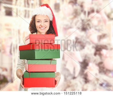 Beautiful happy woman in Santa hat with Christmas gifts on blurred decorated fir tree background. Christmas shopping concept.