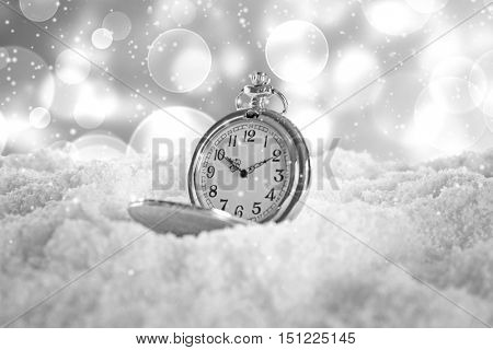 Vintage pocket watch on snow against blurred background. Christmas concept.