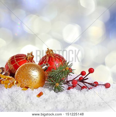 Christmas decoration on snow against bright blurred background.