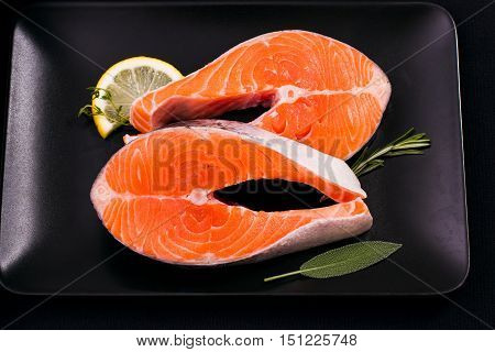Two delicious raw salmon slice with spices on black plate, top view