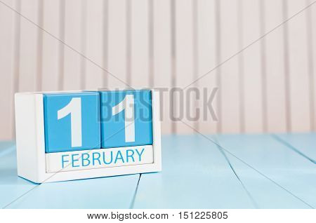February 11th. Day 11 of month, calendar on wooden background. Winter concept. Empty space for text.