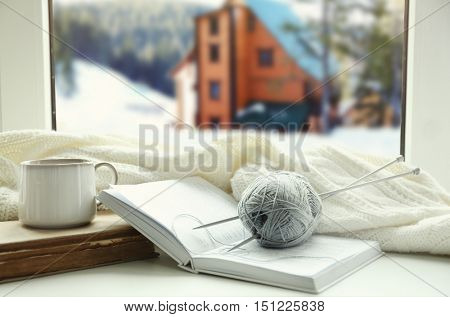 Cup of hot drink and book on the windowsill in winter landscape background