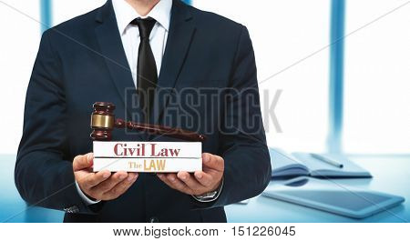 Male hands with law books and judge gavel on blurred office background. Justice concept.