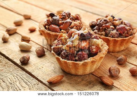 Delicious nut cakes on wooden table