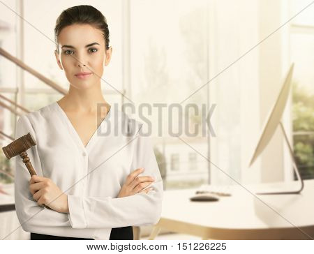 Beautiful woman with judge gavel on blurred office background. Justice concept.