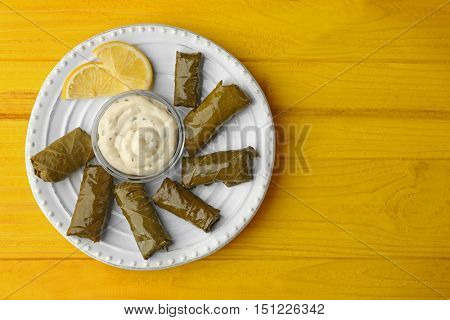A plate of delicious stuffed Dolma with sauce and lemon on yellow wooden background