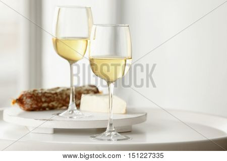 Glasses with white wine, cheese and wurst on a table