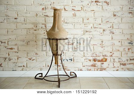Ancient amphora on stand on brick wall background