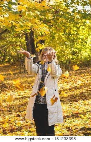 Portrait of mature attractive woman playing with autumn