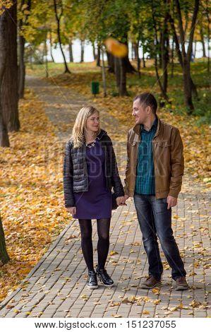 Beautiful pregnant couple walking in autumn Park