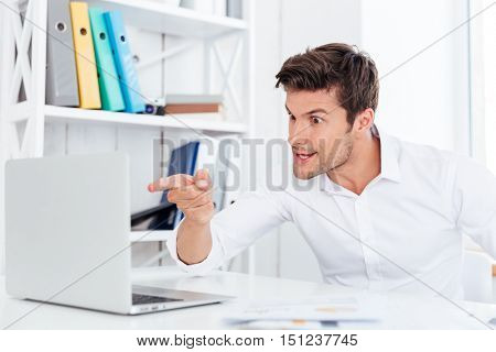 Angry annoyed businessman pointing finger at laptop while sitting at the office desk