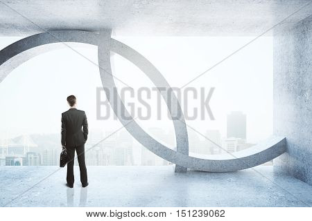 Back view of businessman in concrete interior with city view and daylight. 3D Rendering