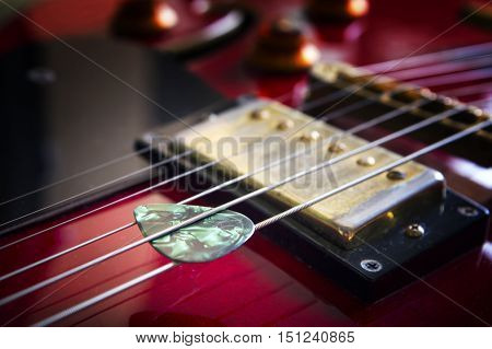 Red acoustic guitar with plectrum close up in dark background