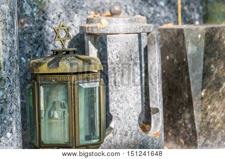 candle lantern on the stone grave in Yiddish cemetery